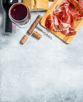Traditional spanish ham with ciabatta and red wine. on a rustic background.