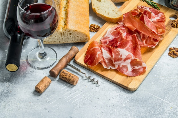 Traditional spanish ham with ciabatta and red wine. on a rustic.