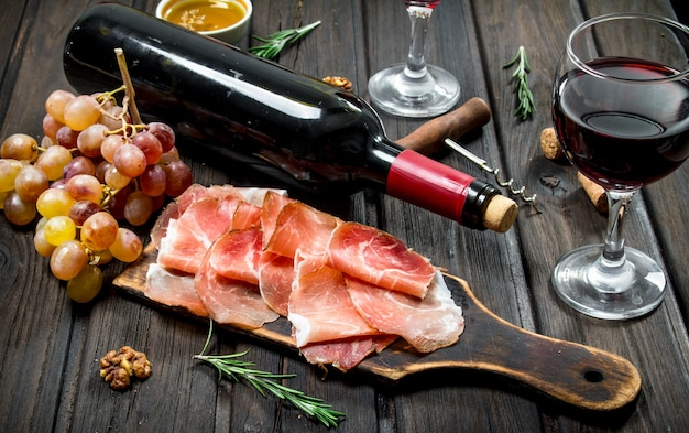 Traditional spanish ham with grapes and red wine. on a wooden background.
