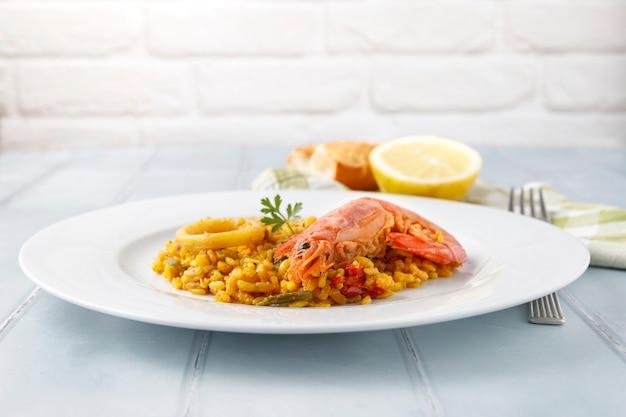 シーフードと野菜を添えた伝統的なスペインのパエリアを皿と青いテーブルでお召し上がりいただけます
