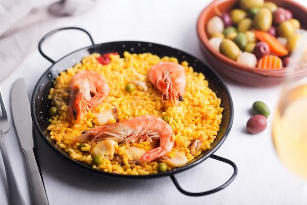 Традиционная испанская паэлья с морепродуктами. подготовлено в традиционной кастрюле