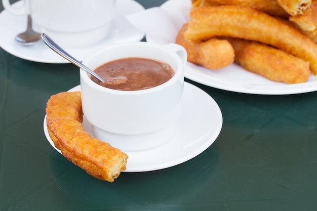 伝統的なスペインのペストリー-チュロスとチョコレートの白いカップ