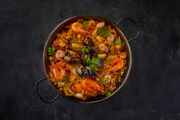 Traditional spanish seafood paella in the fry pan on a black background