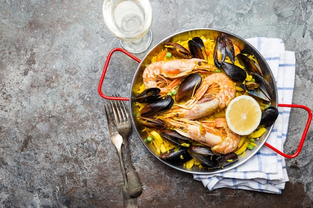 Traditional spanish seafood paella in a fry pan over gray,