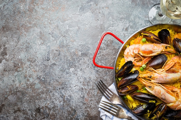 Traditional spanish seafood paella in a fry pan over gray