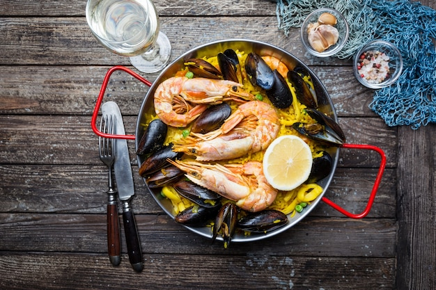 Traditional spanish seafood paella in a fry pan on a wooden old table,