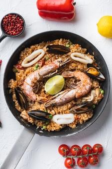 Традиционная испанская паэлья из морепродуктов в сковороде на белом фоне
