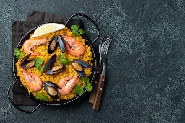 ひよこ豆、エビ、ムール貝、黒いコンクリートの背景にイカと鍋で伝統的なスペインのシーフードパエラ。コピースペースのある上面図