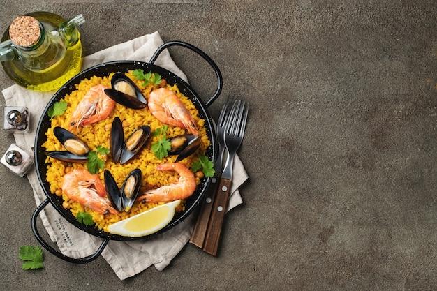 ひよこ豆、エビ、ムール貝、茶色のコンクリートの背景にイカと鍋で伝統的なスペインのシーフードパエリア。コピースペースのある上面図