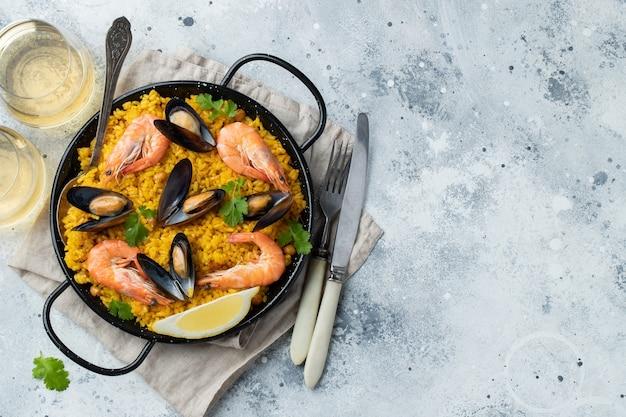ひよこ豆、エビ、ムール貝、ライトグレーのコンクリートの背景にイカと鍋で伝統的なスペインのシーフードパエリア。コピースペースのある上面図