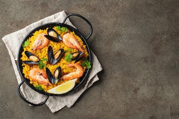 병아리 콩, 새우, 홍합, 오징어와 함께 냄비에 전통적인 스페인 해산물 빠에야. 평면도.