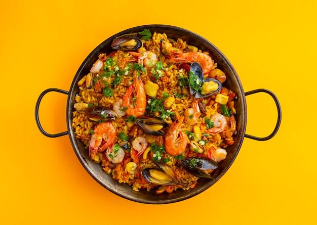 Традиционная испанская паэлья из морепродуктов в сковороде на фоне