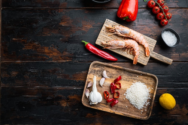 Traditional spanish seafood paella ingredients on old wooden dark table, top view with space for text, food photo.