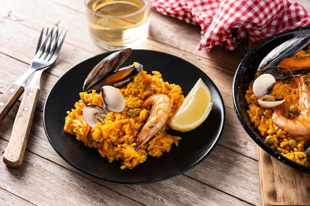 Традиционная испанская паэлья из морепродуктов на деревянном столе
