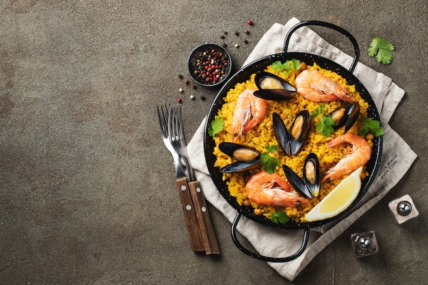 Traditional spanish seafood paella in pan with chickpeas, shrimps, mussels, squid. top view.