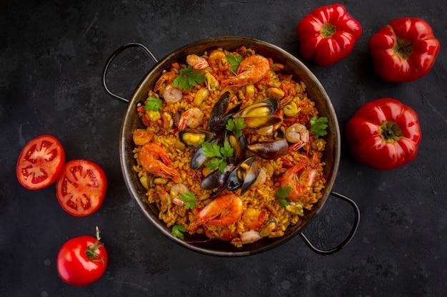 Традиционная испанская паэлья из морепродуктов с помидорами на черном фоне