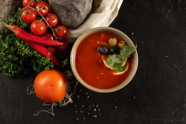 伝統的なスペインのスパイシートマトスープガスパチョとオリーブとオリーブ。