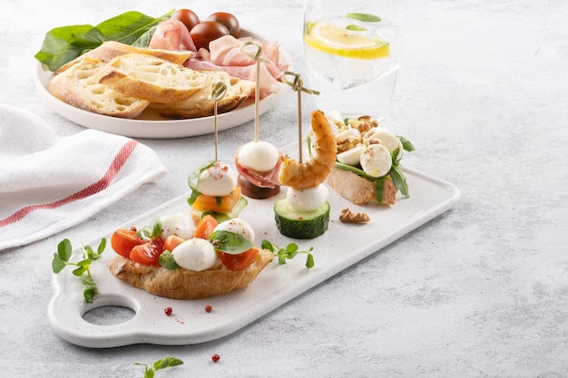 Traditional spanish tapas appetizer pinchos with mozzarella cucumbers shrimp and prosciutto