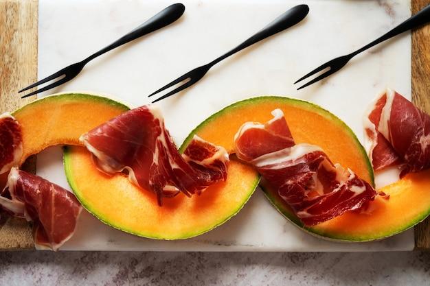 ピンクの背景の上に大理石のサービングボードにバジルとメロンを添えた伝統的なスペインのタパスハモンイベリコ。前菜、タパス、前菜料理のコンセプト、