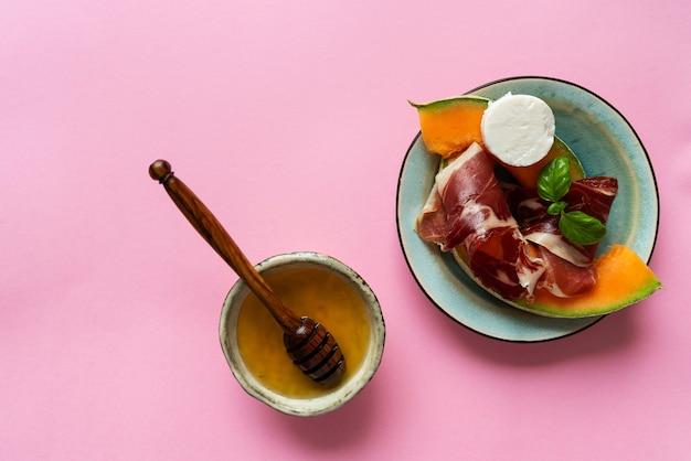 素朴な背景に山羊のチーズ、メロン、蜂蜜を添えた伝統的なスペインのタパスハモンイベリコ。上面図。フラットレイ。