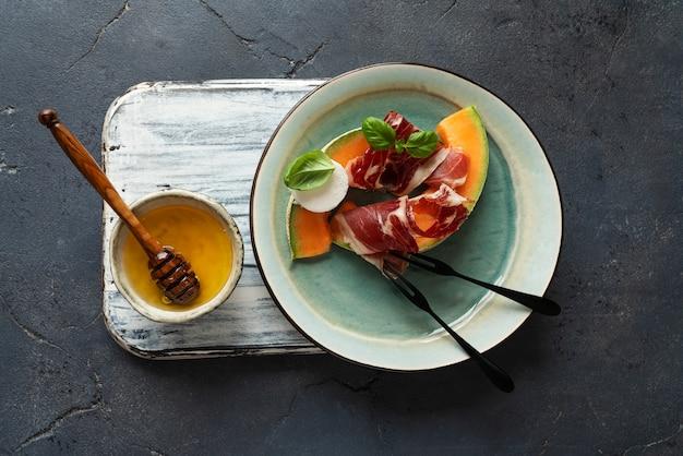 素朴な背景に山羊のチーズ、メロン、蜂蜜を添えた伝統的なスペインのタパスハモンイベリコ。上面図。フラットレイ