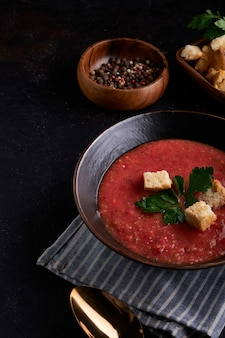 Traditional spanish tomato soup gazpacho with spice in black bowl