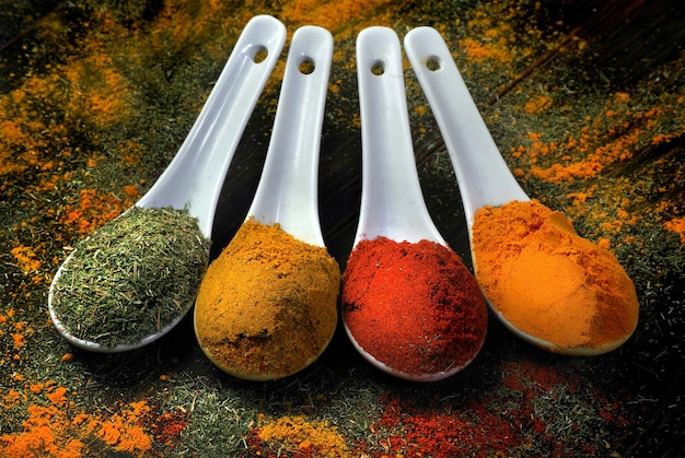 Traditional spices. chili pepper, turmeric, curry and dry dill in spoons on the table.
