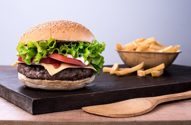 Traditional spicy beef burger with salad and tomato on top of a wooden board and white table