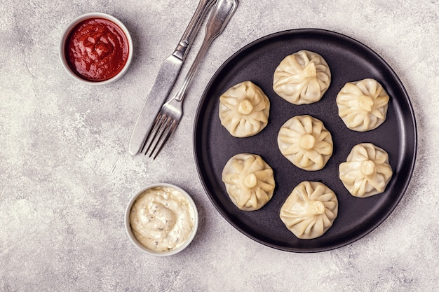 Traditional steamed dumplings khinkali with tomato and tartar sauce
