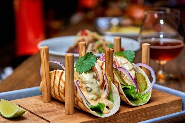 Традиционные уличные мексиканские тако из свинины с говядиной, авокадо, чили и луком в желтой кукурузной лепешке.