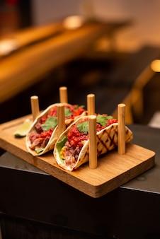 Традиционные уличные мексиканские тако из свинины с говядиной, помидорами, авокадо, перцем чили и луком в желтой кукурузной лепешке под названием al pastor