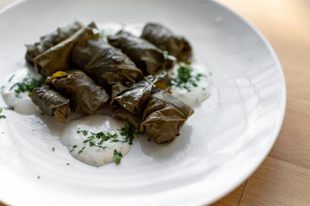Традиционные фаршированные виноградные листья на большой белой тарелке с соусом