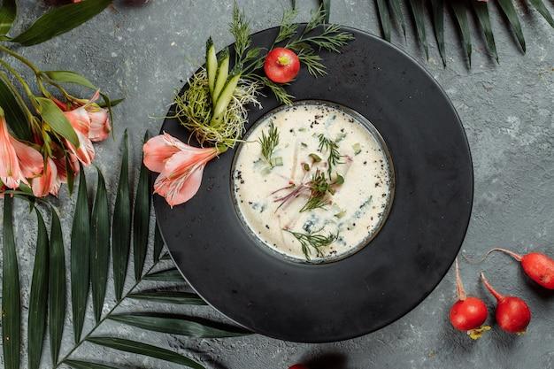 Традиционный летний русский холодный суп с квасом, окрошка с ветчиной и овощами, еда.