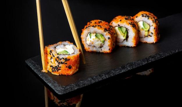 검은 배경에 전통 스시와 젓가락 일본 요리