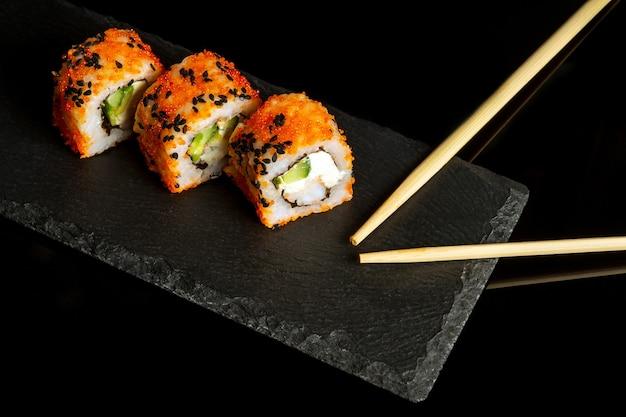 Традиционные суши и палочки для еды. филадельфия с лососем, авокадо и сыром. японская кухня на черном фоне.