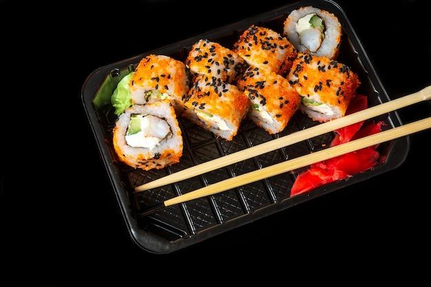 Традиционные суши и палочки для еды филадельфия с лососем, авокадо и сыром