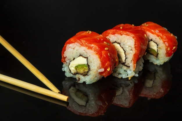 Traditional sushi and chopsticks - philadelphia with salmon, avocado and cheese