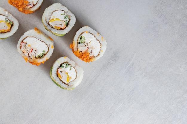 Rotoli di sushi tradizionali decorati con patatine croccanti su fondo di pietra.