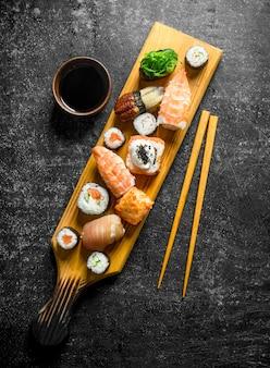 まな板の上に醤油と箸で巻いた伝統的な巻き寿司。暗い素朴な背景に