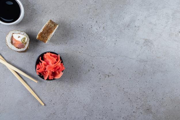 돌 배경에 참치와 절인 생강으로 전통적인 스시 롤.