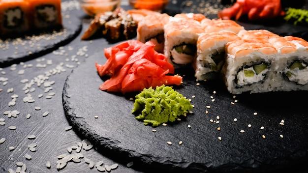 Традиционные специи для суши маринованные имбирь и васаби. японская еда. роллы с креветками на темном фоне