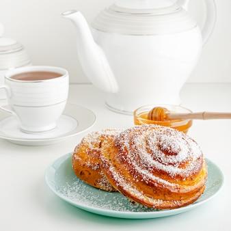 Traditional swedish fika or cinnamon bun on white breakfast table. square image