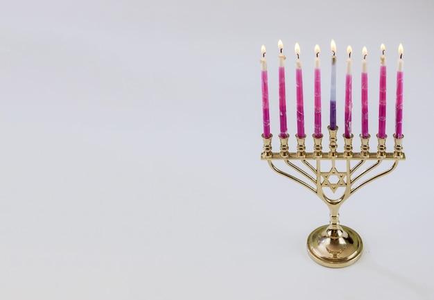 燃えるろうそくとハヌカの伝統的なシンボルヘブライ本枝の燭台は、白い孤立した背景のユダヤ教の祝日