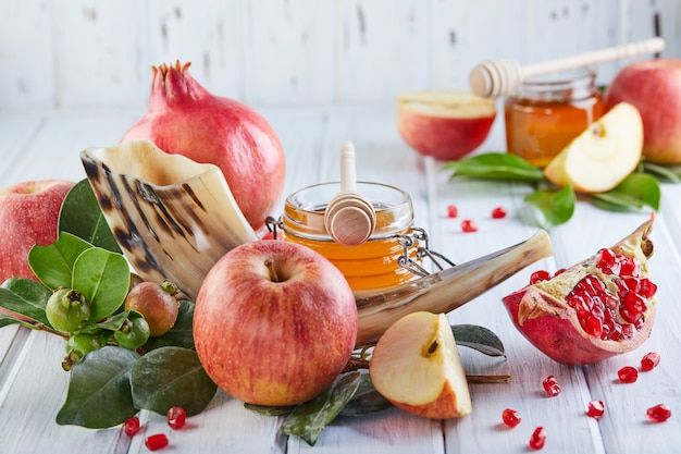 Traditional symbols: honey jar and fresh apples with pomegranate and shofar- horn on white wooden.