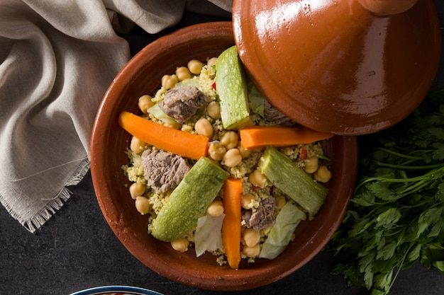 Traditional tajine with vegetables, chickpeas, meat and couscous on black slate. top view
