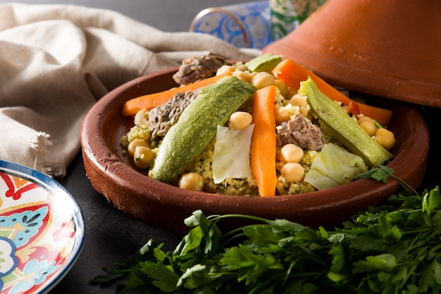 Traditional tajine with vegetables, chickpeas, meat and couscous on black slate