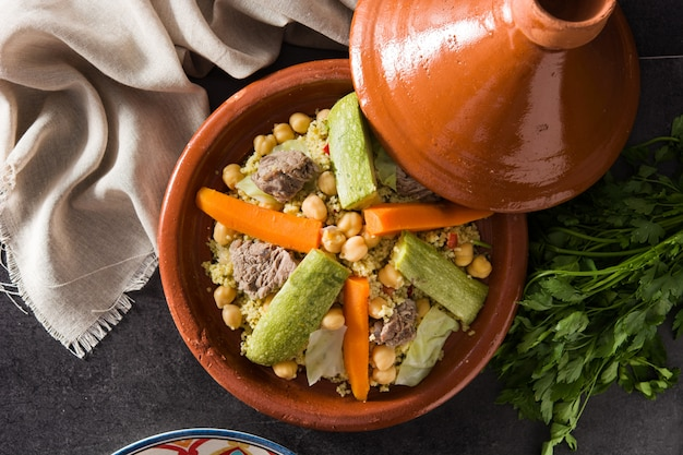 Traditional tajine with vegetables, chickpeas, meat and couscous on black