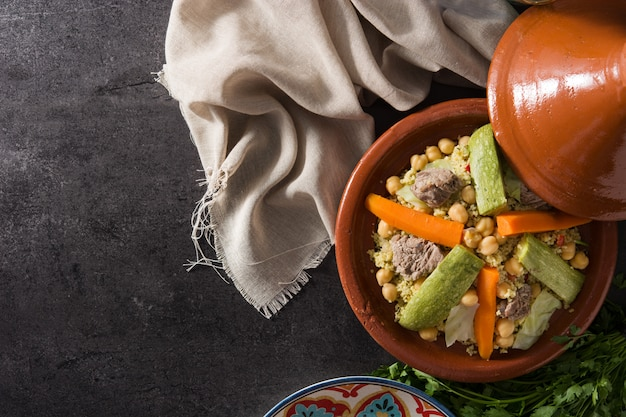 Traditional tajine with vegetables, chickpeas, meat and couscous on black.