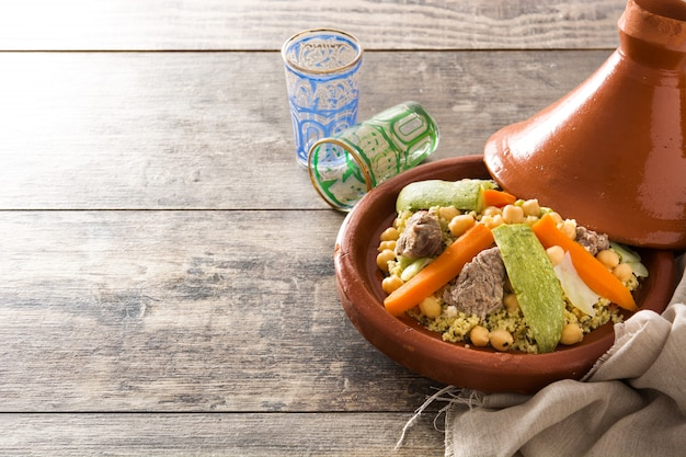 Traditional tajine with vegetables, chickpeas, meat and couscous on wooden table.
