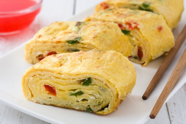 Traditional tamagoyaki japanese omelette on white wooden table close up